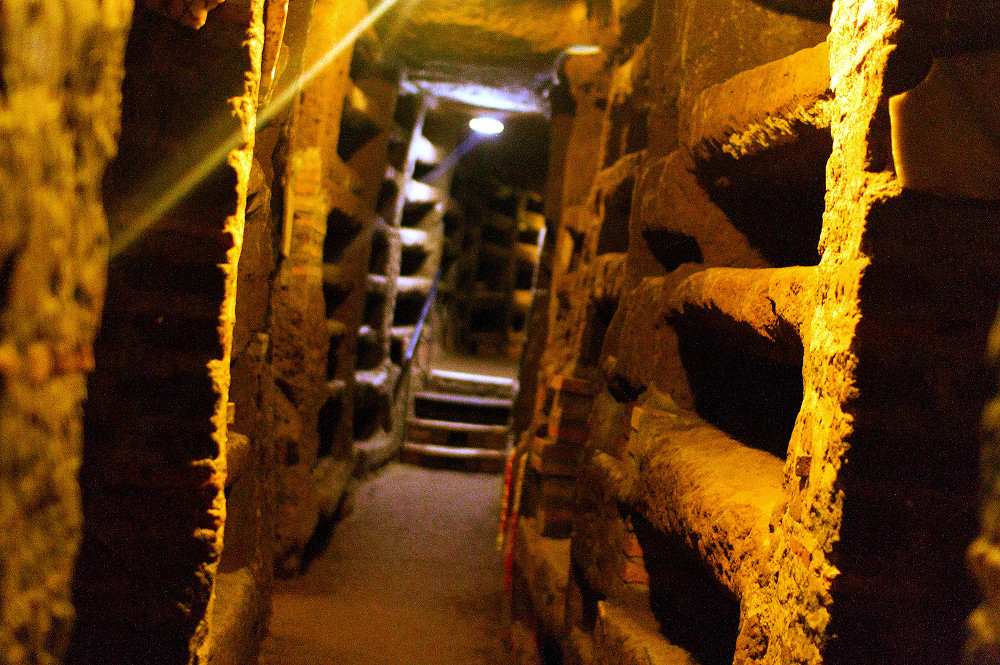 Exploring underground Rome, narrow tunnel inside Priscilla catacombs. Photo courtesy of Walks of Italy