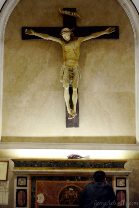 Woman praying at the altar of one of the side chapels